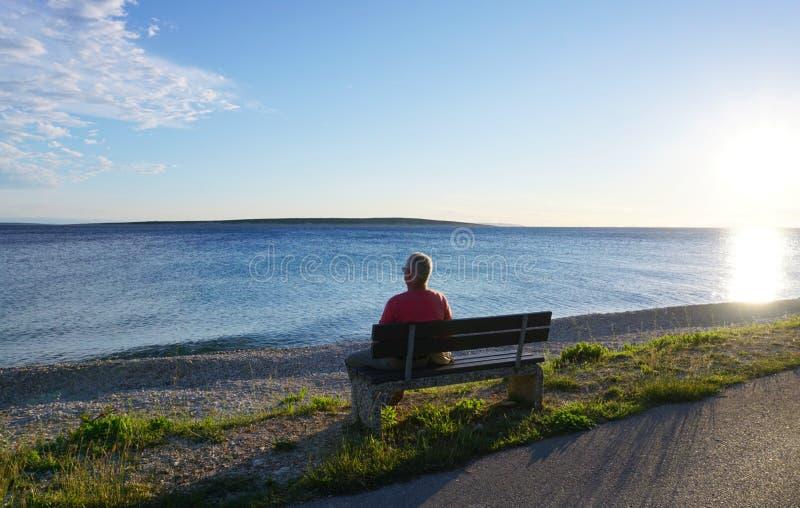 Mandre, isola del PAG, Croazia, il 22 giugno 2018 Uomo anziano che si siede sul banco dal mare e che osserva nella distanza il tr fotografie stock