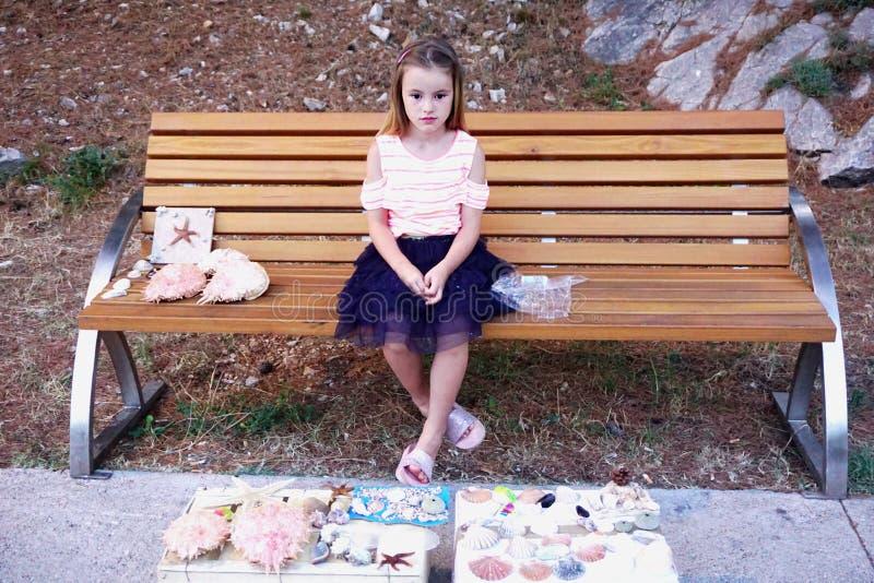 Mandre Kroatien, Juli 20, 2019 En gullig liten flicka sitter på bänken och säljer snäckskalen royaltyfri fotografi