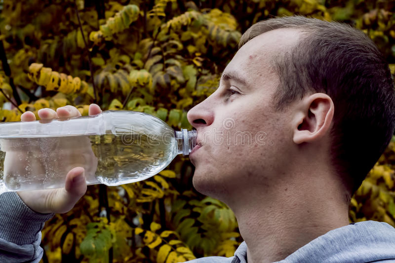 Mandricksvatten från en flaska utanför arkivbild
