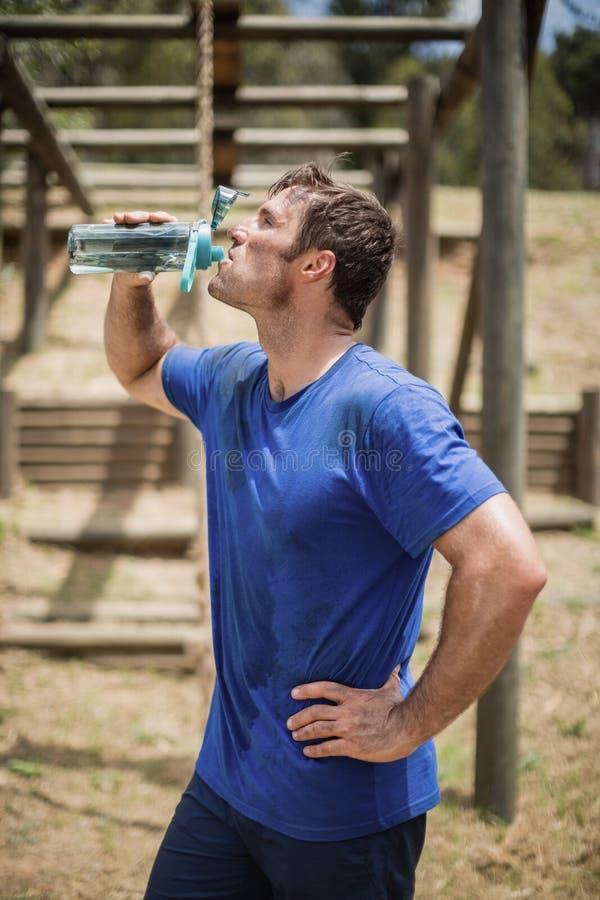 Mandricksvatten från flaskan under hinderkurs royaltyfri fotografi