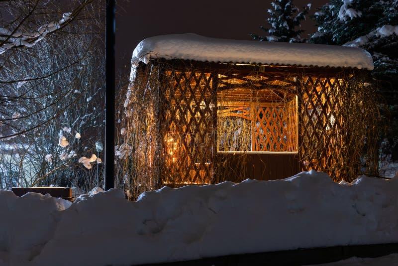Mandril de uma ?rvore na noite do inverno com ilumina??o Cabana de madeira bonita no tempo de inverno com ?rvores e luz fotos de stock royalty free