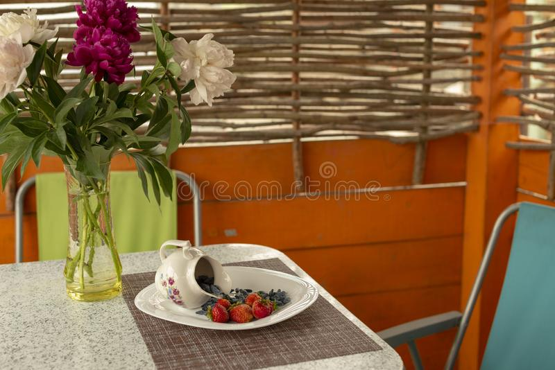 Mandril do ver?o O café da manhã da luz de Utrenny das bagas Uma madressilva com um morango silvestre e um creme de leite imagens de stock