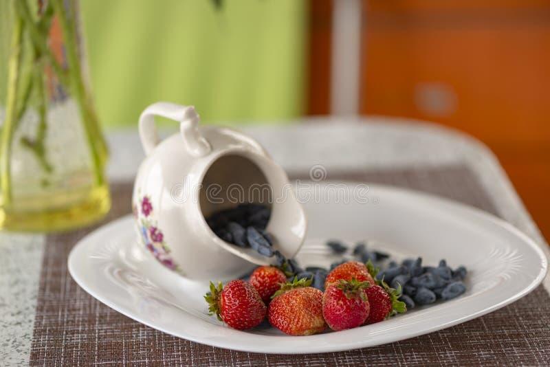 Mandril do ver?o O café da manhã da luz de Utrenny das bagas Uma madressilva com um morango silvestre e um creme de leite fotos de stock