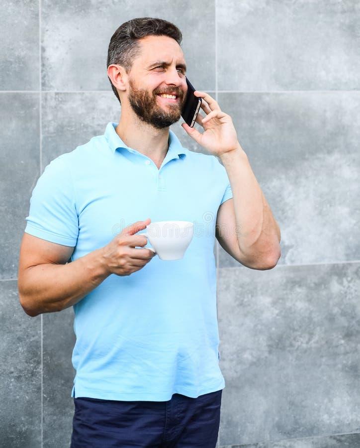 Mandrinkcappuccino talar grå väggbakgrund för telefonen Om även du dricker kaffe på gå, är varje smutt det lilla avbrottet in arkivbilder