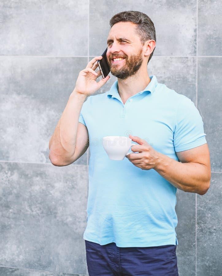 Mandrinkcappuccino talar grå väggbakgrund för telefonen Om även du dricker kaffe på gå, är varje smutt det lilla avbrottet in arkivfoton