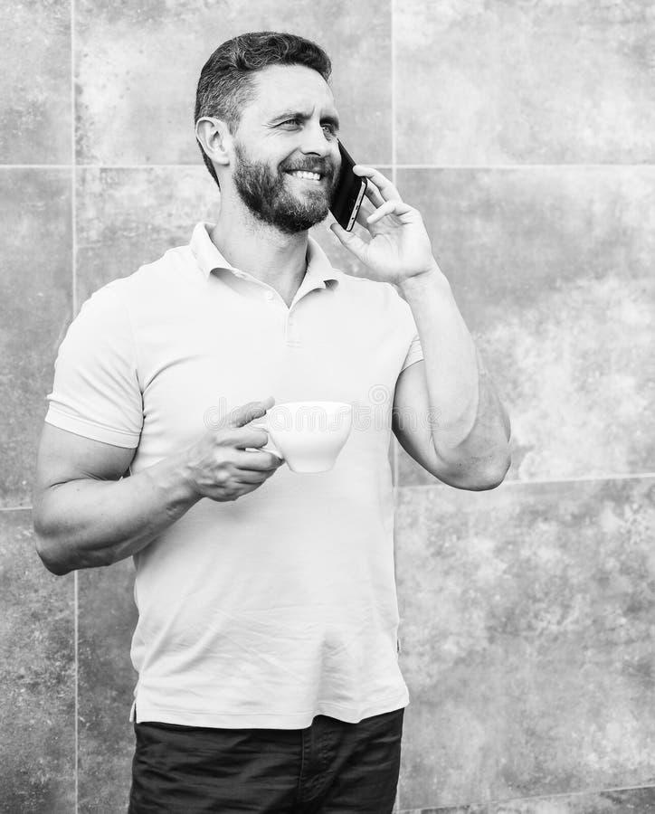 Mandrinkcappuccino talar grå väggbakgrund för telefonen Om även du dricker kaffe på gå, är varje smutt det lilla avbrottet in royaltyfri foto
