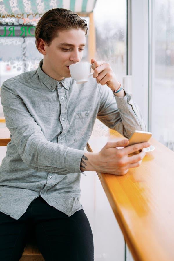 Mandrinkkafé genom att använda livsstil för telefonkaffeavbrott royaltyfria bilder