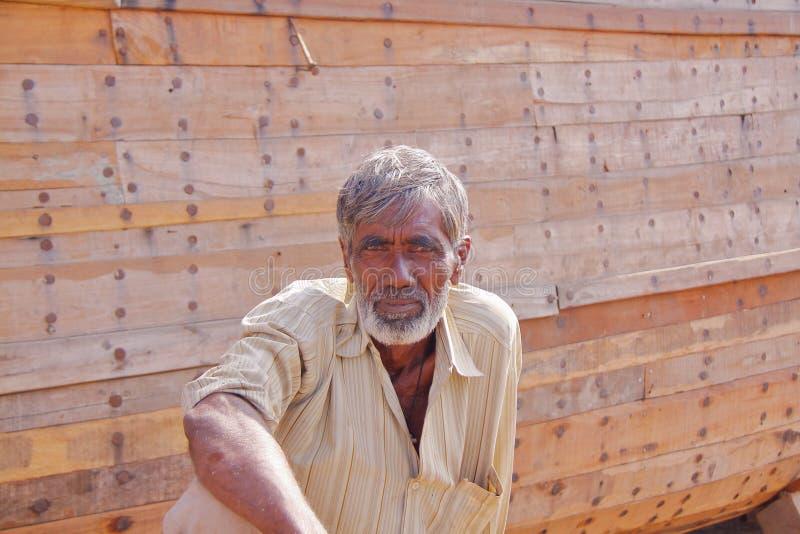 MANDVI, GUJARAT, INDIEN - 21. DEZEMBER 2013: Porträt eines Gujaratimannes, der vor einem traditionellen hölzernen Dhow sitzt stockfotos