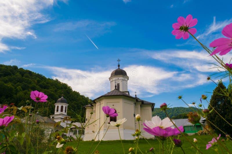 Maneciu, Rumania - 15 de agosto de 2018: La imagen hermosa de Suzana Monastery tiró a través de las flores coloridas Maneciu, Pra imagen de archivo libre de regalías