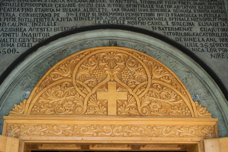 Maneciu, Rumania - 15 de agosto de 2018: La mano hermosa talló el panel sobre la entrada de Suzana Monastery en Maneciu, Prahova, foto de archivo