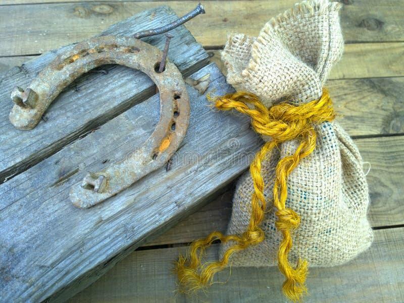 Maneggi il chiodo a ferro di cavallo d'acciaio sui vecchi precedenti di legno immagini stock libere da diritti