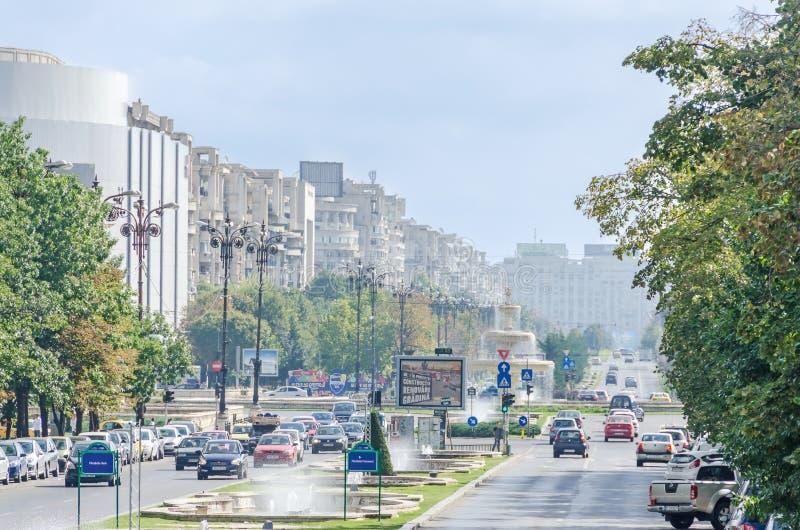 A maneira ao quadrado Piata Unirii com lojas, carros do tráfego, turistas e as fontes exteriores Bucareste, Romania foto de stock