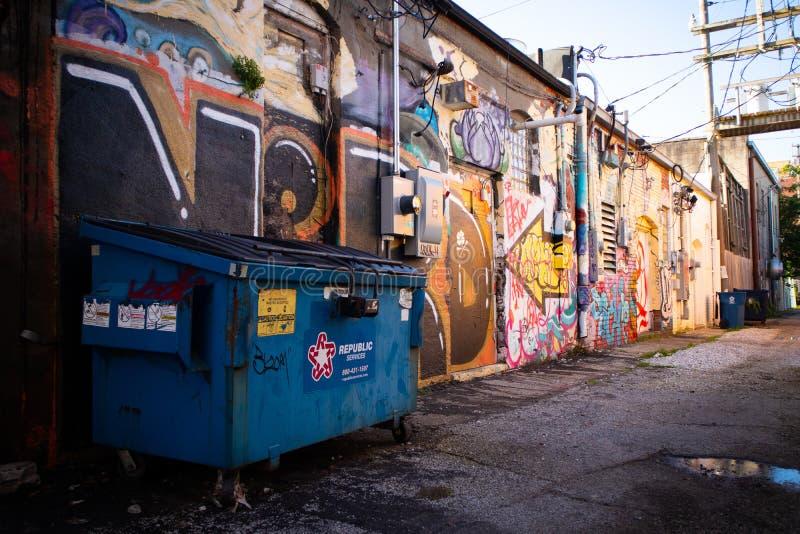 Maneira da aleia com grafittis e um contentor fotos de stock royalty free