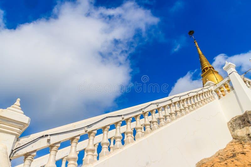 Maneira da escada para cima ao pagode dourado no monte com fundo do céu azul em Wat Khao Rup Chang ou no templo do monte do elefa imagem de stock royalty free