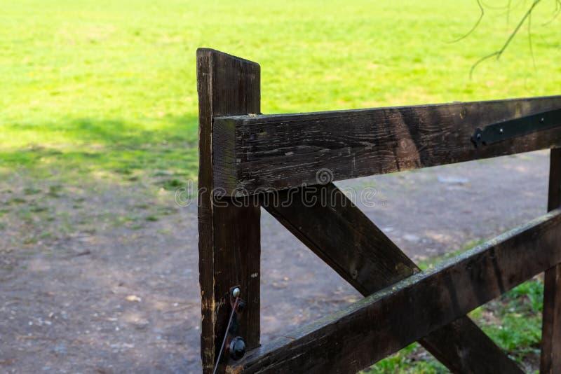 Maneira de madeira da porta à madeira windblown grande velha da porta de wicket do rancho no fundo de um pasto de terra do trajet imagens de stock
