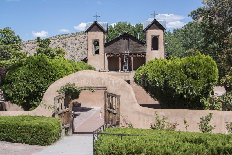 A maneira histórica da entrada de Santuario De Chimayo na capela do marco de Roman Catholic Church do adôbe em New mexico é um lo imagem de stock royalty free