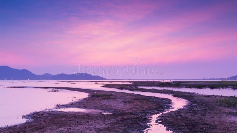 Maneira pequena da água sobre o fundo do lago e da montanha, céu dramático após o por do sol imagens de stock royalty free