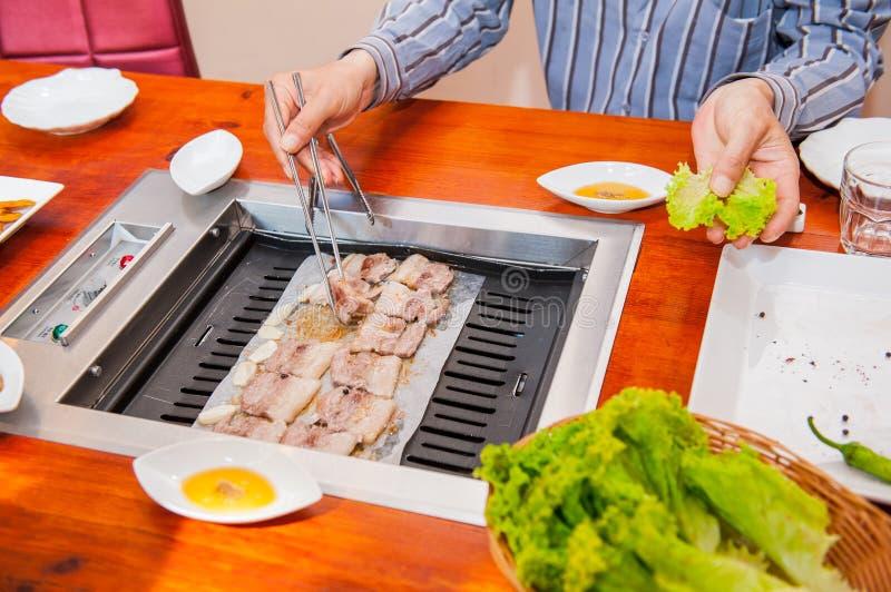 Maneira tradicional de Coreia de comer o prato grelhado na culinária coreana A carne é crua servido, a seguir cozinhado na grade  fotografia de stock royalty free