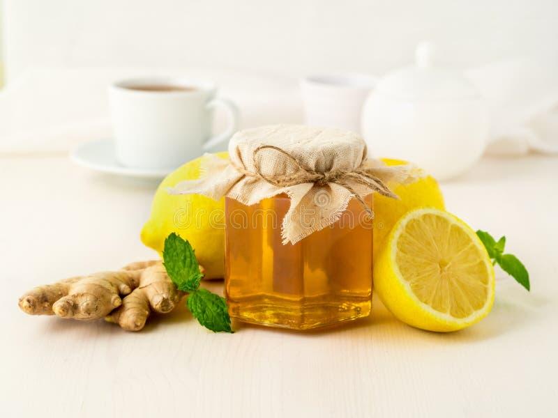 Maneiras populares de tratar um frio - um frasco do mel, gengibre, hortelã, lem fotografia de stock