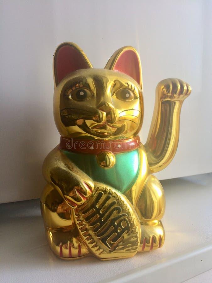 Golden Maneki neko lucky cat. A Maneki-neko plastic cat, symbolizing luck and wealth, on a white background. Toy with swinging arm royalty free stock photo
