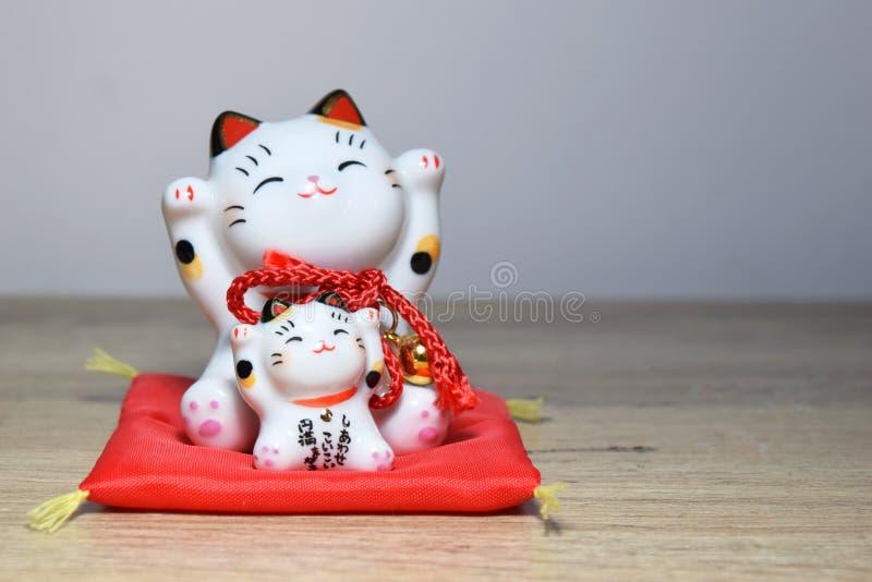 Maneki-neko es una estatuilla japonesa común que tienta el gato fotos de archivo