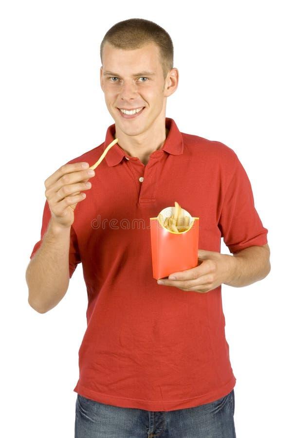 Manen äter pommes frites royaltyfri foto