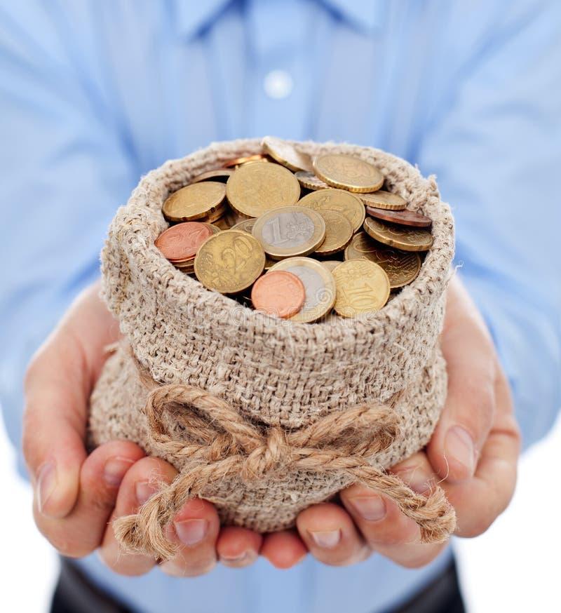 Manen räcker hållande pengar hänger lös med euro myntar arkivfoton