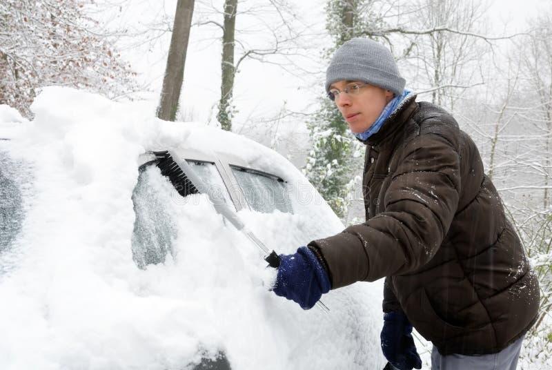 Manen tar bort snow från hans bil royaltyfri foto