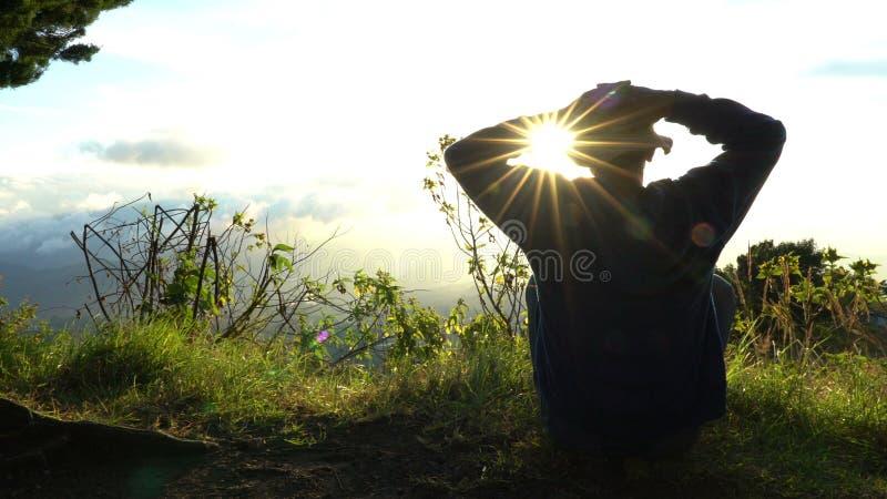 Manenslingmöte upp sollöneförhöjning på kanten av berg Göra meditation i solljus arkivfoton