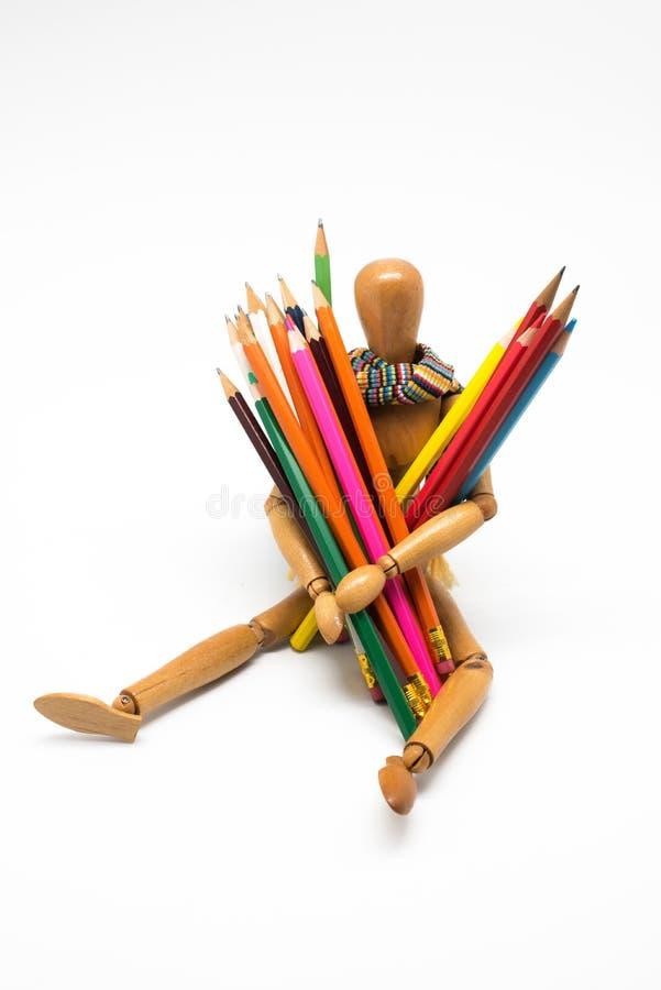 Manequim de madeira com pinturas coloridas, de volta ? escola imagens de stock
