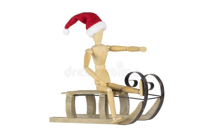 Manequim de madeira em um trenó que veste um chapéu de Santa imagem de stock royalty free