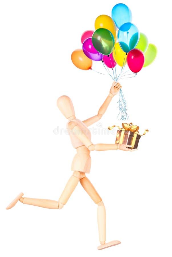 Manequim de madeira que guarda o presente e que voa balões foto de stock royalty free