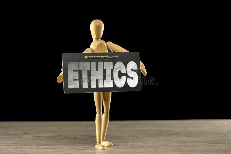 Manequim de madeira que guarda um sinal das éticas imagens de stock