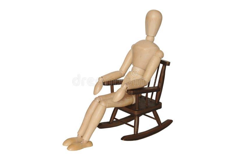Manequim de madeira que senta-se na poltrona foto de stock