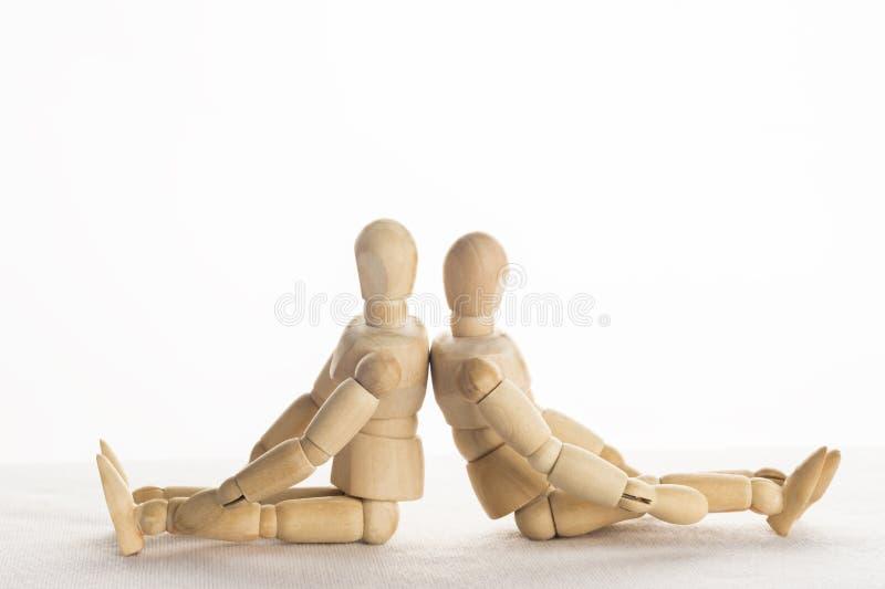 Manequim de madeira Sit Back Facing Each outro no backg do branco do isolado foto de stock