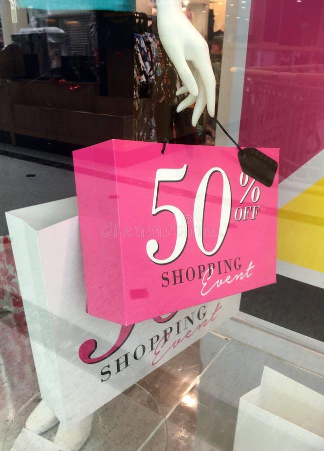 Manequim do boutique que guarda o sinal da venda no saco de compras imagem de stock