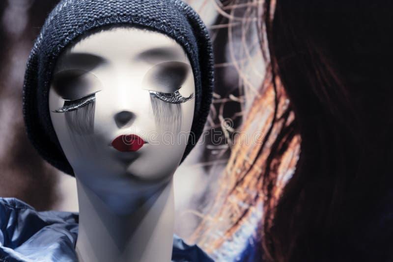 Manequim principal fêmea em uma loja com bordos vermelhos, pele branca e as pestanas longas fotografia de stock