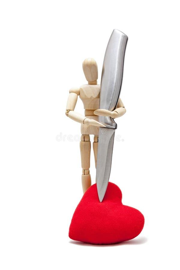 manequins de madeira com uma faca cortante em um coração vermelho, isolado imagens de stock