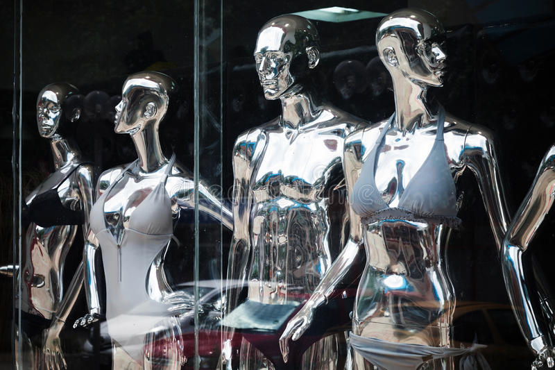 Manequins metálicos de brilho que estão em uma janela fotografia de stock