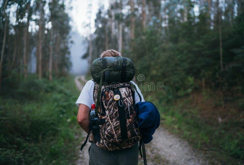 Manera de hembra del backpacker del peregrino de Saint James que pasa por la trayectoria a través de lanzamiento trasero de la im fotos de archivo libres de regalías