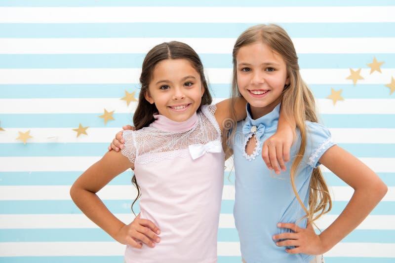 manera de los cabritos las pequeñas muchachas bonitas demuestran la moda de los niños niñas con sonrisa en caras imagen de archivo