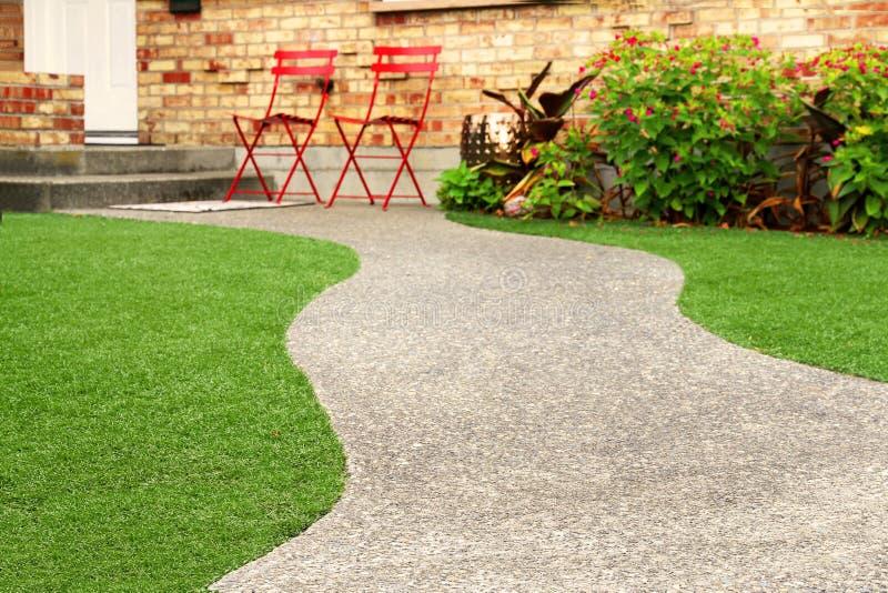 Manera del paseo con la hierba perfecta que ajardina con la hierba artificial en área residencial foto de archivo