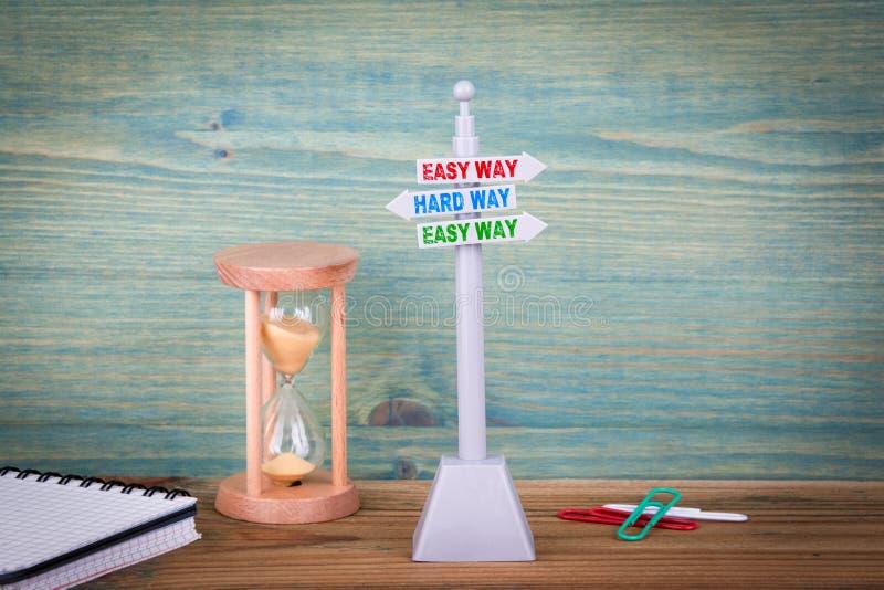 Manera fácil y manera dura Poste indicador en la tabla de madera imagen de archivo libre de regalías