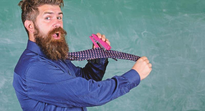 Manera peligrosa de la grapadora desaliñada del uso del hombre La corbata del desgaste formal del profesor del inconformista sost foto de archivo