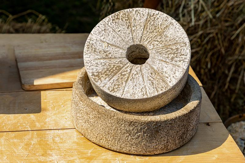 Manera tradicional hecha a mano de pulido de la producción de la harina del grano de la piedra de la piedra de molino con antigüe fotos de archivo libres de regalías