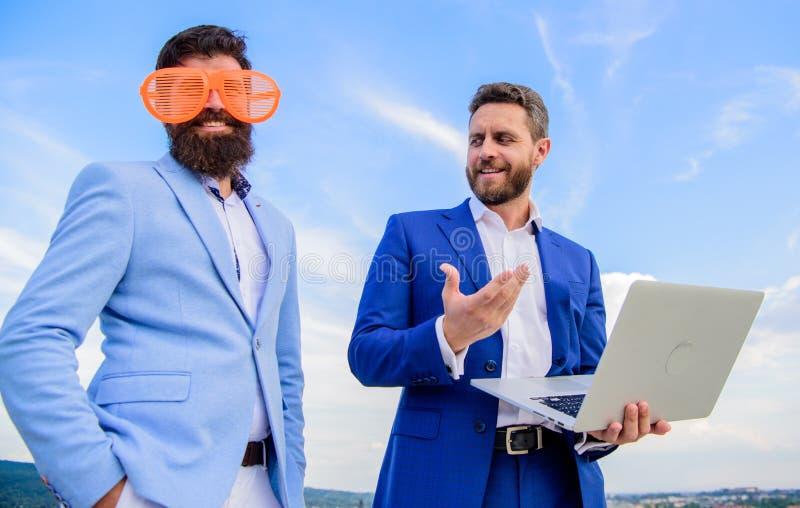 Maneras de conseguir a gente tomarle seriamente Hombre de negocios con el ordenador portátil serio mientras que vidrios ridículos fotografía de archivo