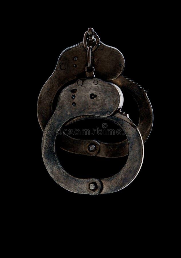 Manette d'acciaio dell'attrezzatura speciale della polizia, fetters su un fondo nero immagine stock libera da diritti