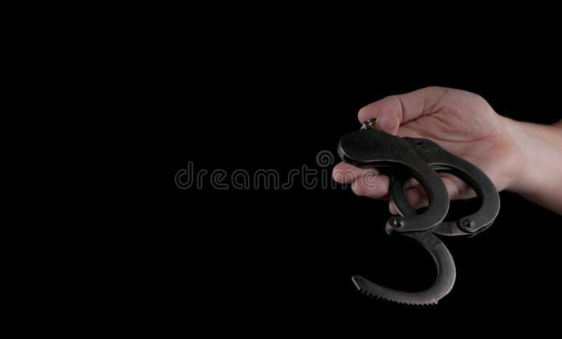 Manette d'acciaio dell'attrezzatura speciale della polizia, fetters su un fondo nero fotografia stock libera da diritti