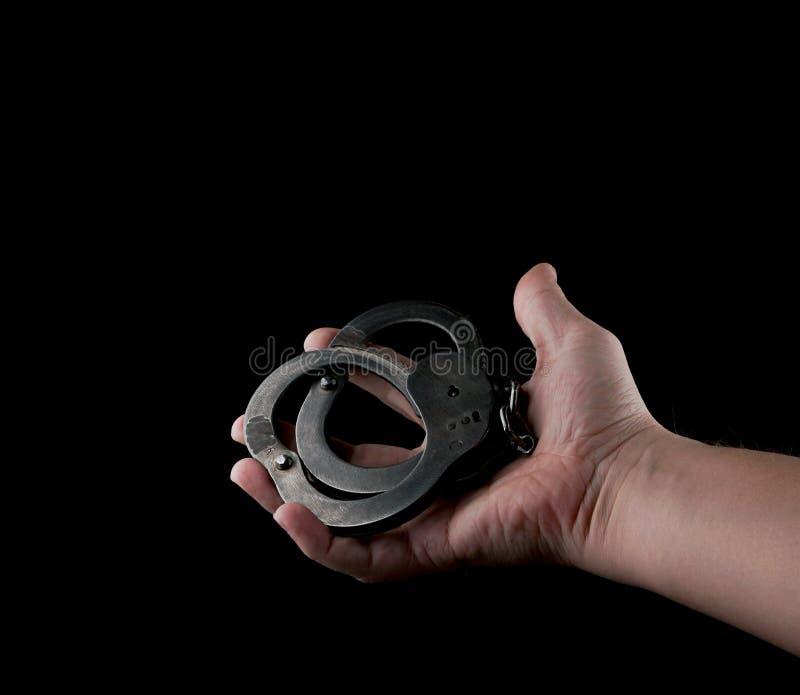 Manette d'acciaio dell'attrezzatura speciale della polizia, fetters su un fondo nero immagini stock