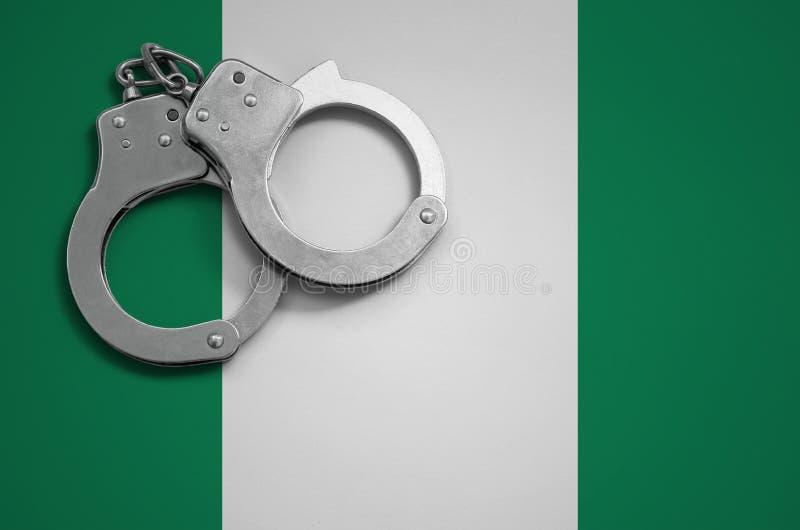 Manette della bandiera e della polizia della Nigeria Il concetto del crimine e delle offese nel paese fotografia stock libera da diritti